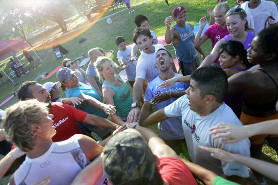 Rob Oliphant encourages other participants in Camp Gladiator as he leads a huddle during a boot camp session at Stude Park. Photo: Cody Duty, Houston Chronicle