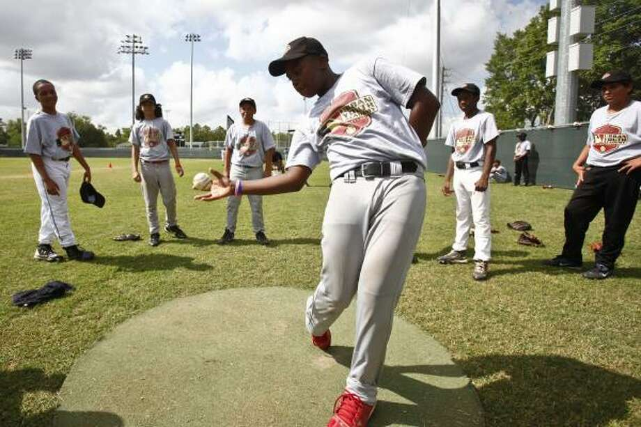 Hunter Branch, 14, practices a batting hand-eye coordination drill during a summer baseball camp at the Houston Astros MLB Urban Youth Academy at Sylvester Turner Park. The academy provides individual instruction from former college players. Photo: Michael Paulsen, Chronicle