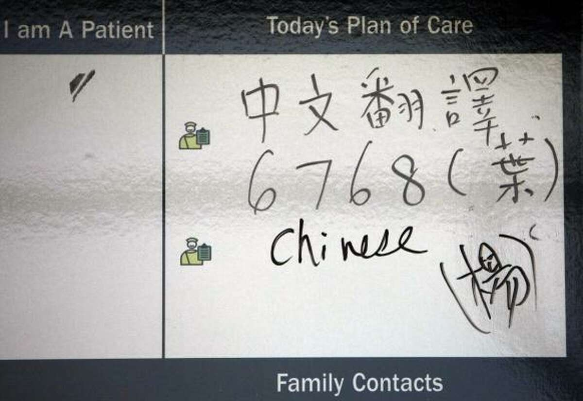 On the whiteboard of a patient's room are instructions on how to call for Chinese translation services.