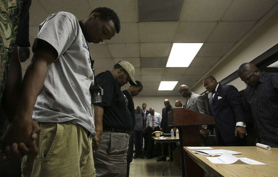 Everly James, 21, joins in a closing prayer Wednesday at a seminar led by activist Quanell X at Houston's Sunnyside Mutli-Service Center. The forum was for ex-offenders trying to find jobs and featured 10 business owners who have served time in prison. Photo: Karen Warren, Chronicle