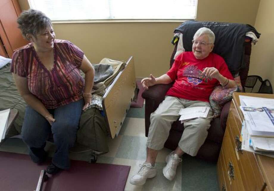 Sharon Steahle, left, a volunteer with AssistHers, visits with Casey Davis, 90, at a nursing home on Friday. Photo: Melissa Phillip, Chronicle
