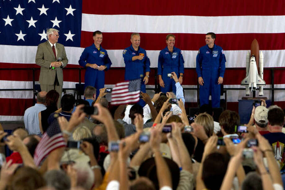 "The crowd at Ellington Field on Friday try to get snapshots of the final shuttle crew. Johnson Space Center director Mike Coats joins the ""final four"" on stage: from left, Commander Christopher Ferguson, pilot Doug Hurley, Sandra Magnus and Rex Walheim. Photo: Johnny Hanson, Chronicle"