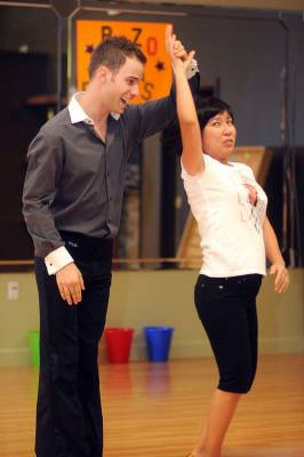 Alex Armaos teaches salsa dancing to Tina Bui of Kingwood during a group lesson at the Fred Astaire Studio in Atascocita. Photo: Jerry Baker, For The Chronicle