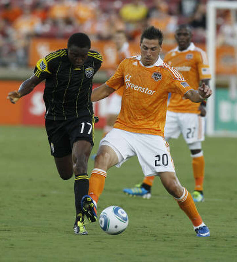 Columbus' Emmanuel Ekpo battles for the ball with the Dynamo's Geoff Cameron in the first half on Saturday night. Photo: Karen Warren, Chronicle