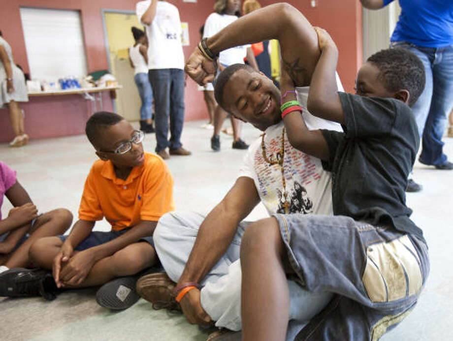 Cornelius Long, a Texas Southern University student participant in iServe Third Ward, plays with Jerald Thompson III, 10, right, and Kemmar Thompson, 6, in the Cuney Homes housing project's community building, near the TSU campus. Photo: Nick De La Torre, Chronicle