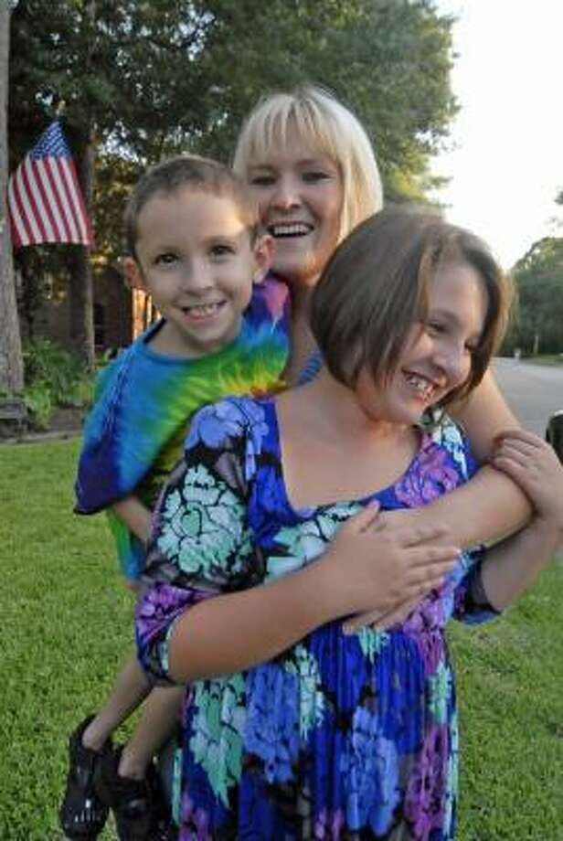 TONY BULLARD: FOR THE CHRONICLE PART OF THE FAMILY: South African au pair Claudia Coetzee hugs Christian Whitt, 7, and Elizabeth Whitt, 10, at their home in Cypress. Coatzee has signed on to care for the children for a year. Photo: Tony Bullard, ALL