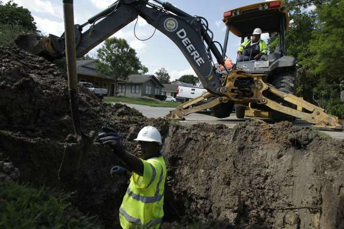 Stanley Hart reaches for a shovel and Richard Flores keeps his backhoe ready as their city crew works on a broken water main Monday in the 2000 block of Alta Vista.