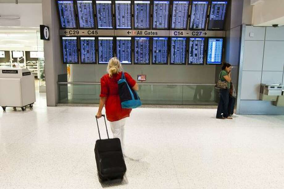 A passenger checks schedules at Bush Intercontinental Airport. A study used Bluetooth, the short-distance wireless technology, to track how long it took passengers to get from the airport's major roadways to Terminal C. Photo: Patrick T. Fallon :, Chronicle