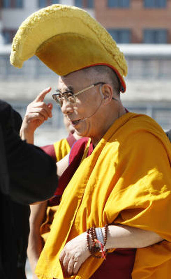 The Dalai Lama dons a ceremonial hat before performing a blessing ceremony at the Anacostia River in Washington on Saturday. His meeting with President Obama was closed to the media. Photo: Jacquelyn Martin, Associated Press