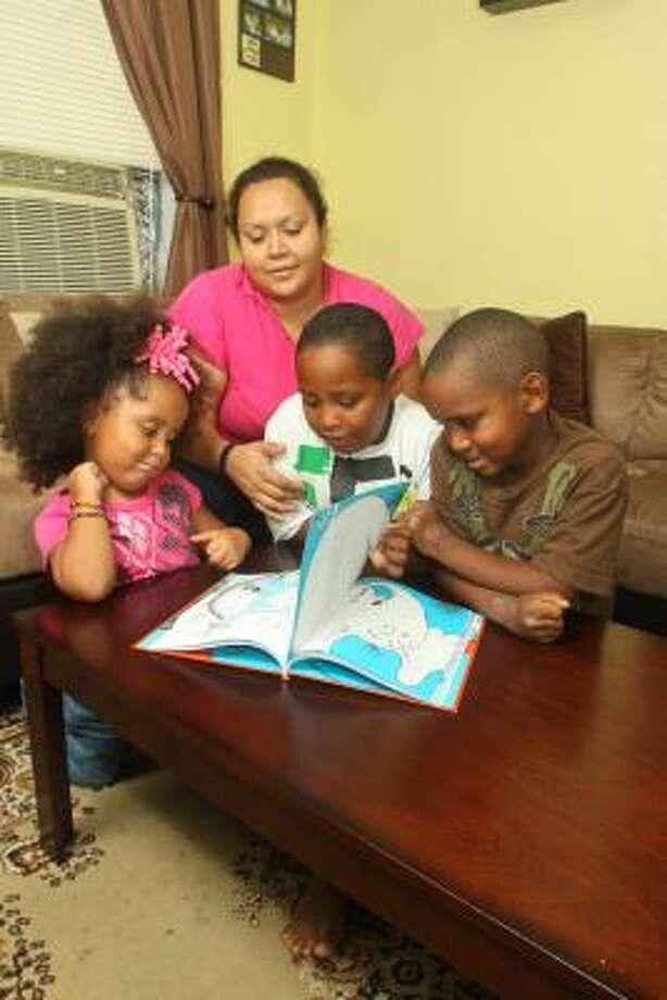 Preparando el regreso a la escuela: Mary Yáñez y sus tres hijos, de izq. a der. Elizabeth, 3, Dante, 7, y Jaden, 6, esperan poder conseguir los útiles escolares a través del YMCA. Photo: Gary Fountain, Para La Voz
