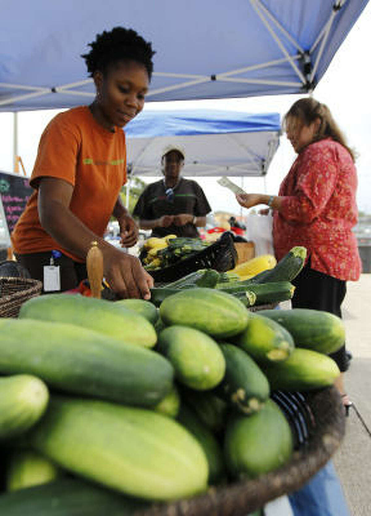 """Jane Momoh gathers vegetables for Maria Buendia, right, at Sunnyside Multi Purpose Center, where the city runs a weekly farmers market called """"Get Moving Houston."""""""