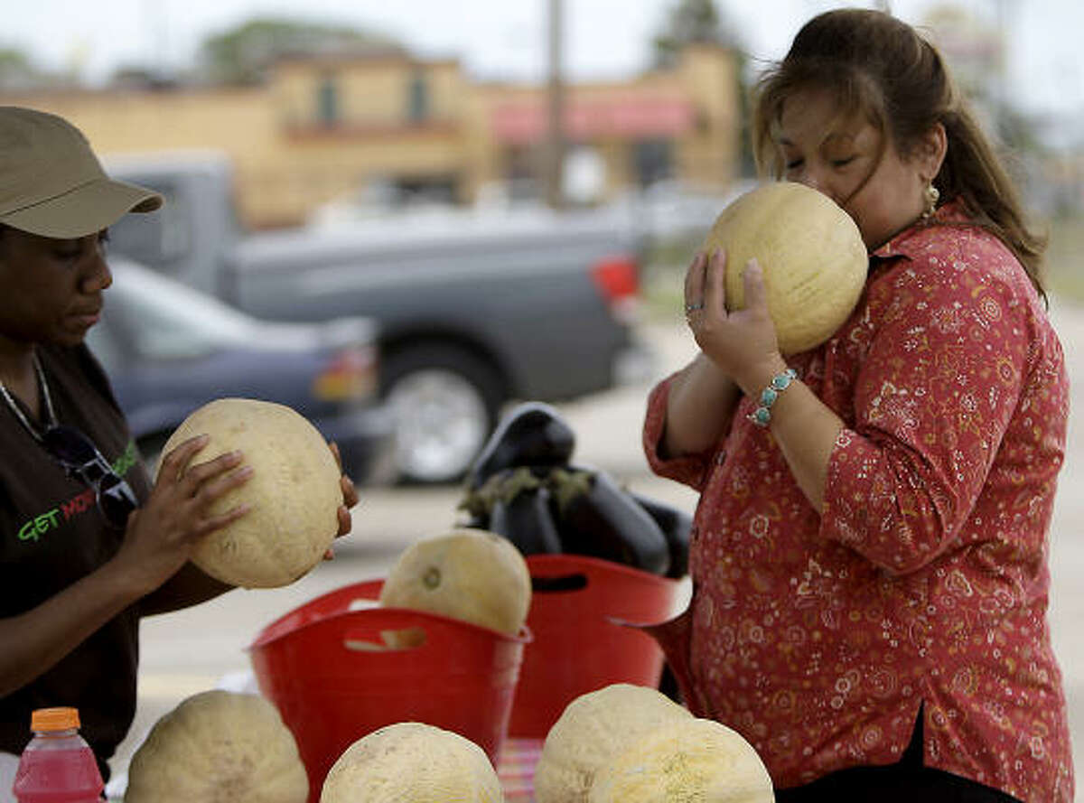 """Maria Buendia takes a whiff to judge the ripeness of a cantaloupe offered by Carol McClung, left, at Sunnyside Multi Purpose Center. The weekly farmers market is part of Houston's effort to combat what are called """"food deserts"""" — neighborhoods where there are few supermarkets or other choices for healthy, affordable food."""