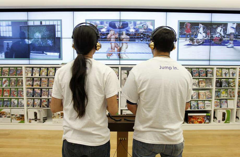 Microsoft Store product advisers Minh Nguyen, left, and Rashid Ballouli demonstrate the gaming center in the new Microsoft Store in the Galleria. The store is Microsoft's first in Texas and 10th around the globe. Photo: Karen Warren :, Chronicle