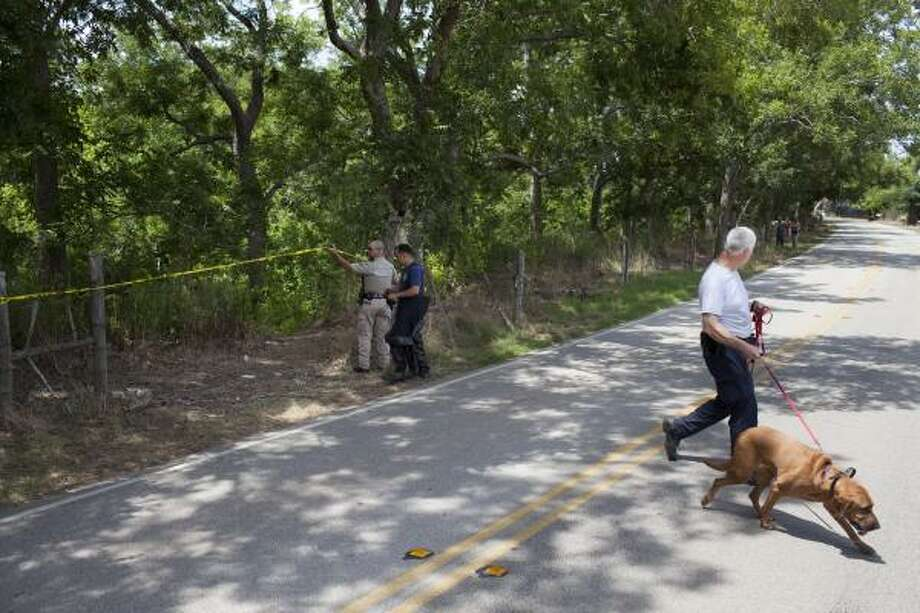 An HPD K-9 officer and a bloodhound were part of the Houston contingent who helped Fort Bend County authorities Monday in the search of Oyster Creek for more of the remains of Laura Jean Ackerson. Photo: Eric Kayne, For The Chronicle