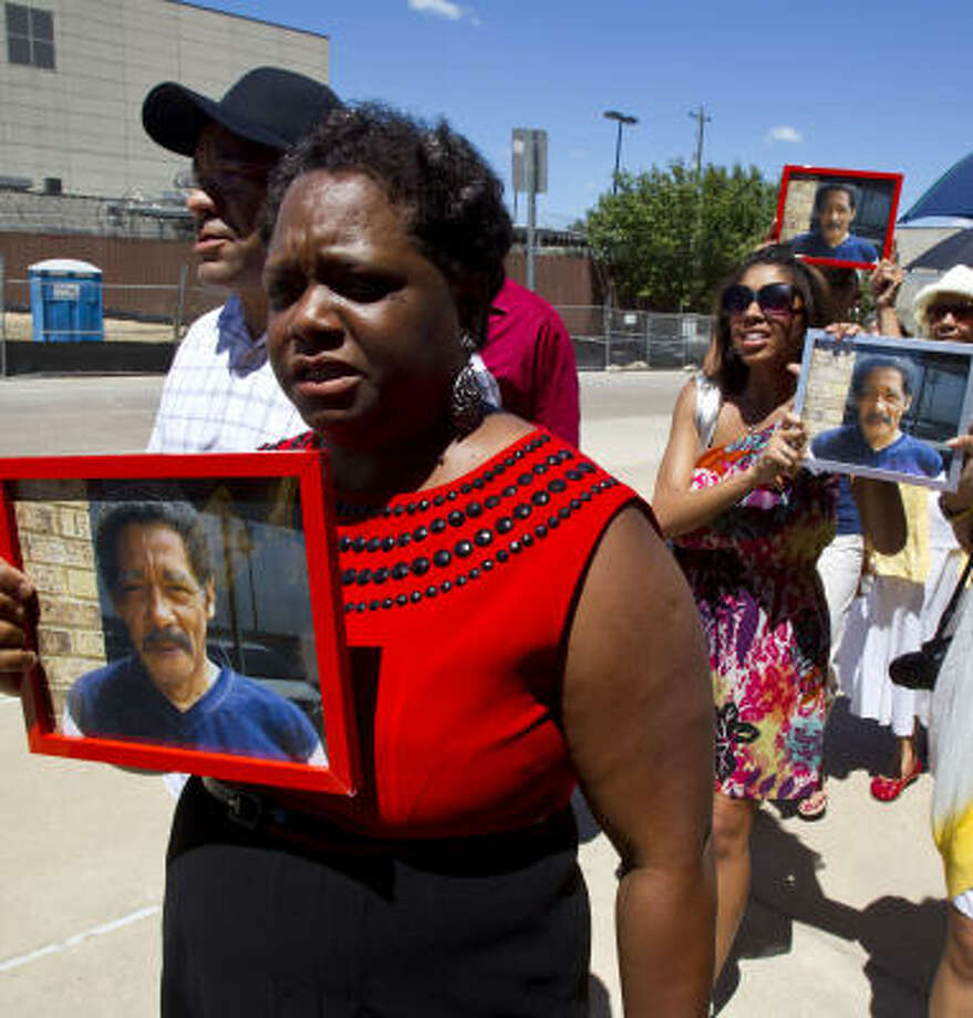 Marie Fields left, carries a photograph of her father, Norman Hicks Sr., during a protest with Quanell  X and other family members in front of the Harris County Jail . Photo: James Nielsen, Chronicle
