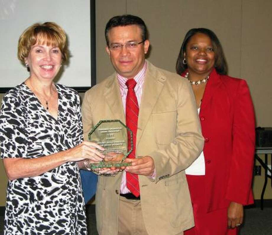 COURTESY PHOTO OUTSTANDING PARTNER: Assistance League of Houston president Jo Pender accepts the Outstanding Community Partner Award for program-wide service to Harris County Department of Education Area I Head Start from Armando Rodriguez, Head Start community coordinator, as Head Start director Venetia Peacock looks on.   The Assistance League provided uniforms to 1,250 Head Start children during the 2010-2011 school year. Photo: Courtesy
