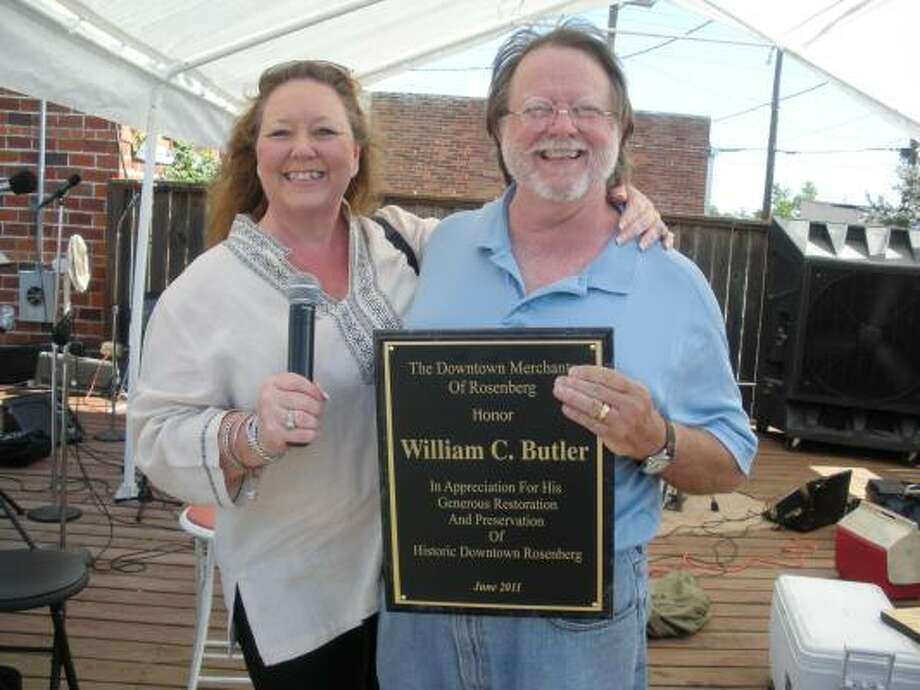 B.J. POLLOCK: FOR THE CHRONICLE SAYING THANKS: Downtown Merchants of Rosenberg President Rae Taylor gives a plaque of recognition to Bill Butler. Photo: B.J. Pollock, For The Chronicle