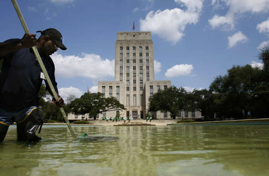 """It's hot in here too,"" Carl Simmons with Houston Parks and Recreation Department said of the hot weather while cleaning the reflecting pool in Hermann Square Monday, June 13, 2011, in Houston. Simmons said he cleans the pool in front of City Hall daily to keep it clean. Photo: Johnny Hanson, Chronicle"