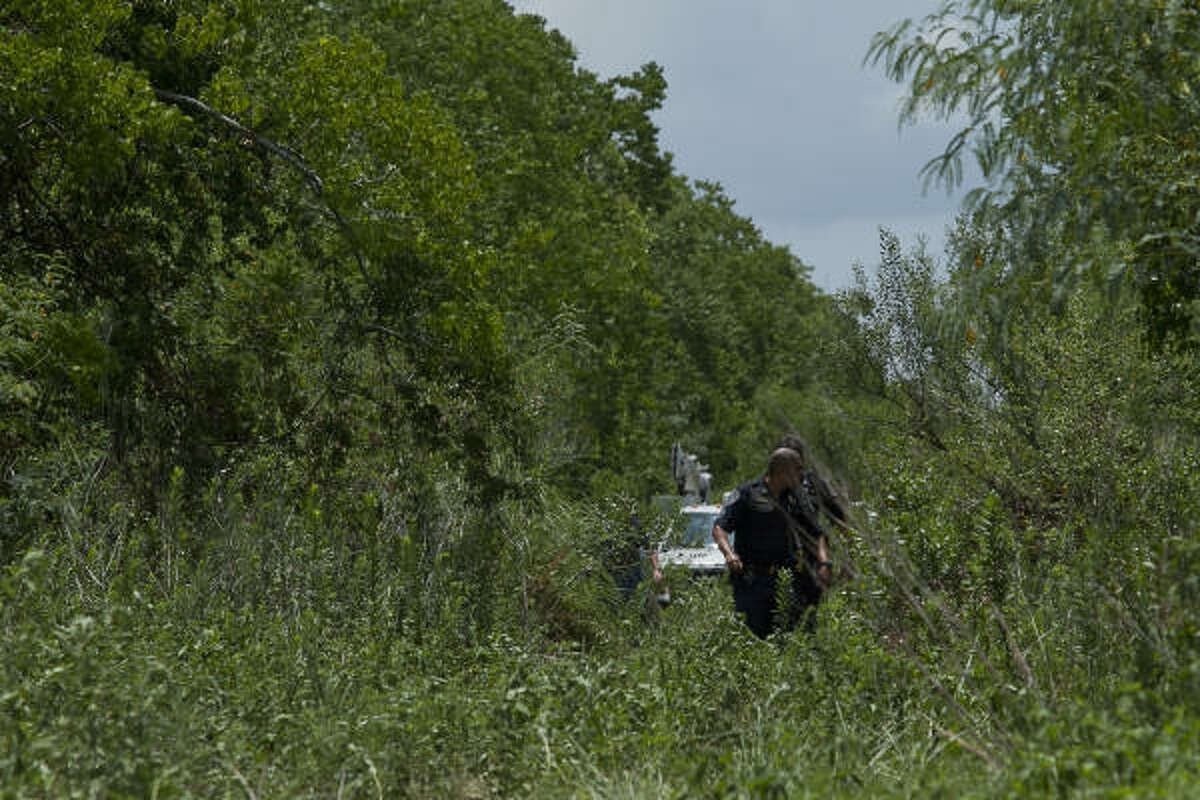 Police officers walk out of the wooded area across from Clear Creek High School in League City on Monday, where a Technical Rescue Unit worked to free 25-year-old Kevin Gonterman.