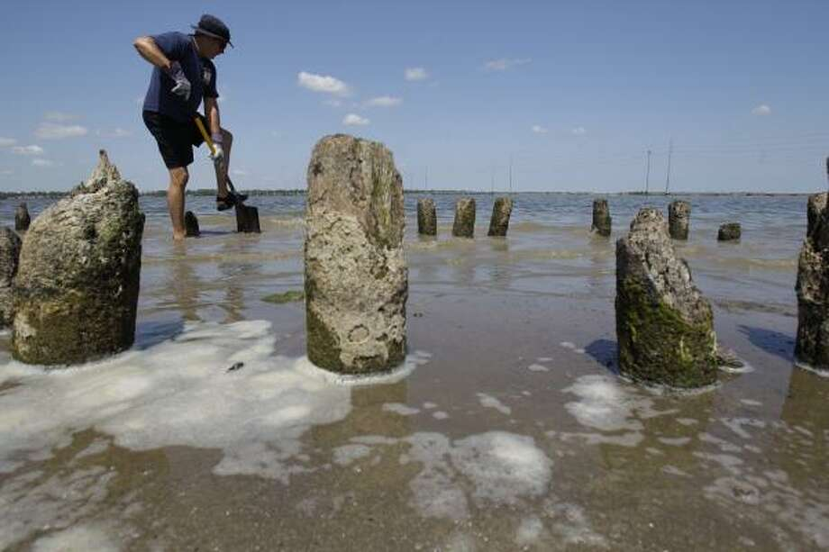 Pilings from a 2-mile-long abandoned railroad trestle that crosses Lake Houston are now visible. Houston Police Lake Patrol officer Gary Crawford readies them for removal on Wednesday. Photo: Melissa Phillip, Chronicle