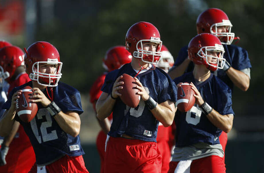 UH quarterbacks Cotton Turner (from left), Crawford Jones, David Piland  and Drew Hollingshead and warm up in practice last year. Jones, Piland and Hollingshead will be competing for the starting job this year. Turner has graduated. Photo: Karen Warren, Chronicle