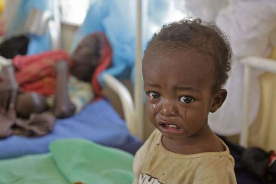 A malnourished child cries at a field hospital of the International Rescue Committee, IRC,  in  Dadaab, Kenya. Dadaab, a camp designed for 90,000 people now houses around 440,000 refugees. Almost all are from war-ravaged Somalia. Some have been here for more than 20 years, when the country first collapsed into anarchy. But now more than 1,000 are arriving daily, fleeing fighting or hunger. Photo: Schalk Van Zuydam, Associated Press