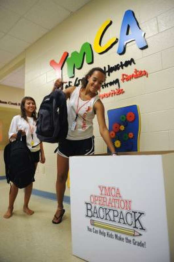 OPERATION BACKPACK: YMCA lifeguards Haley King of northwest Harris County, foreground, and Karen Aristizabal of Bear Creek pitch in with donated backpacks. Photo: Thomas Nguyen, For The Chronicle