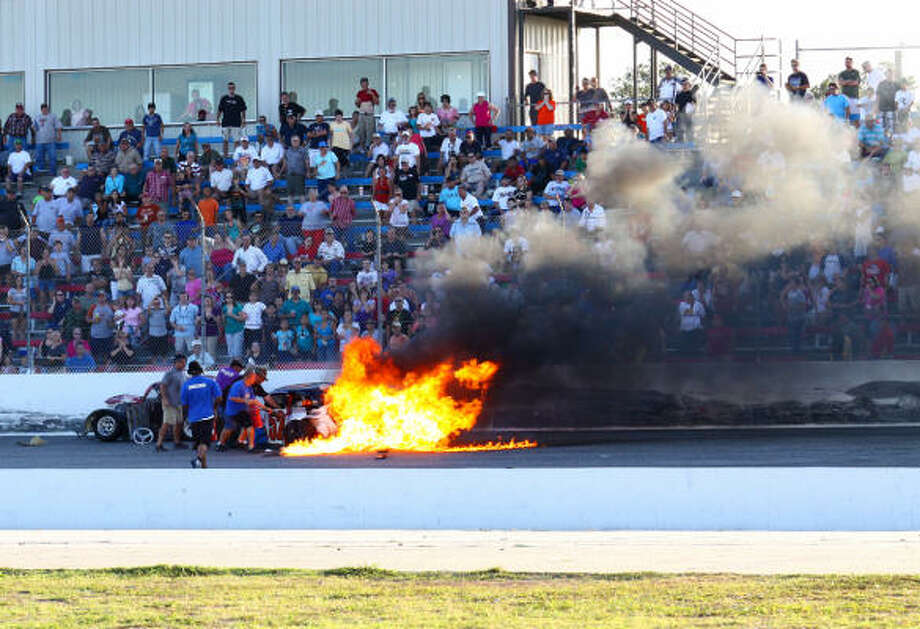 Safety crew members put out the fire in the car driven by Cody Karl after Jake Thomasson ran into the back of Karl during a Legends feature race at Houston Motorsports Park. Neither driver was injured. Photo: Steve Steinle, For The Chronicle