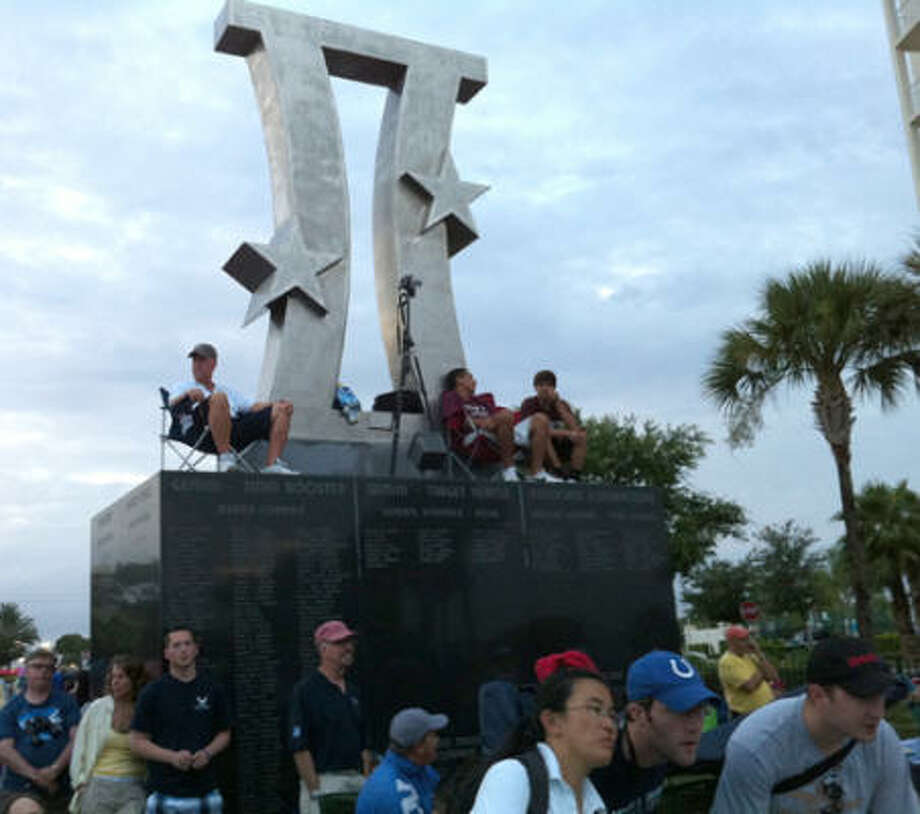 Scott Bigley, 50, John Ramirez, 16, and J.T. Aguilar, 16, of Tarpon Springs, Fla., climbed on top of a monument at Space View Park in Titusville, Fla., after having no luck finding a place among the crowds jockeying for a view of the shuttle Atlantis. Photo: Zain Shauk, Chronicle