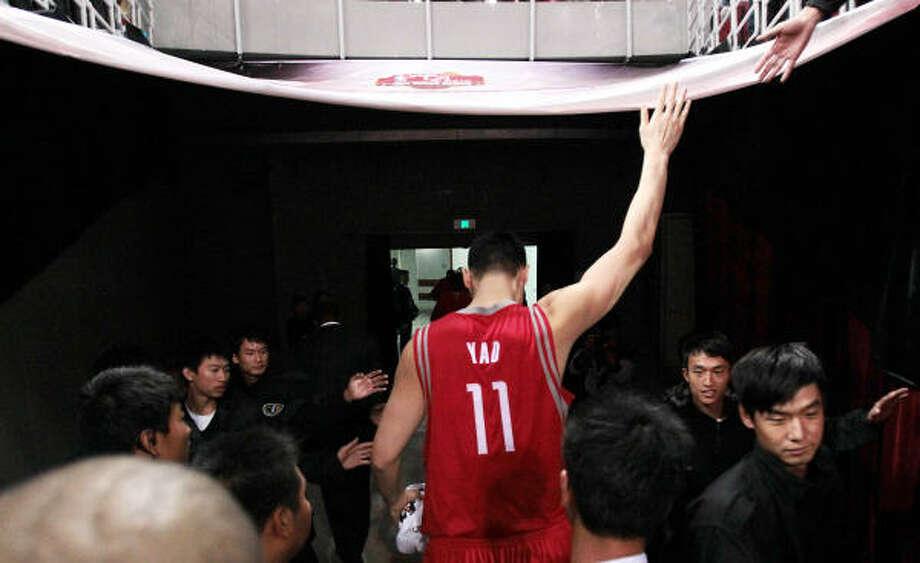 Yao Ming saluda a los aficionados tras un partido de los Rockets contra New Jersey Nets en China. Photo: Billy Smith II, Houston Chronicle