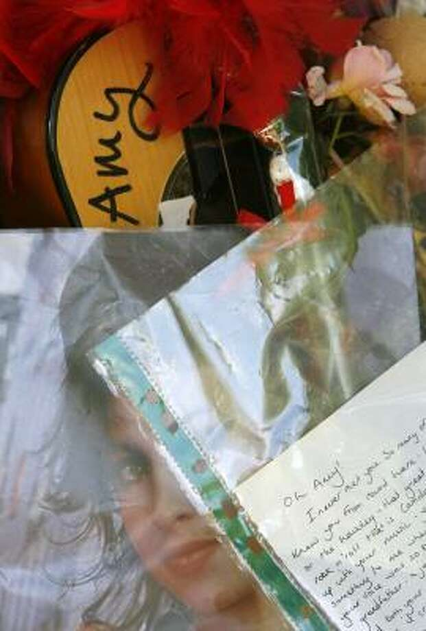 Tributes are seen Sunday outside Amy Winehouse's north London home, where she was found dead the day before. Photo: Akira Suemori, Associated Press