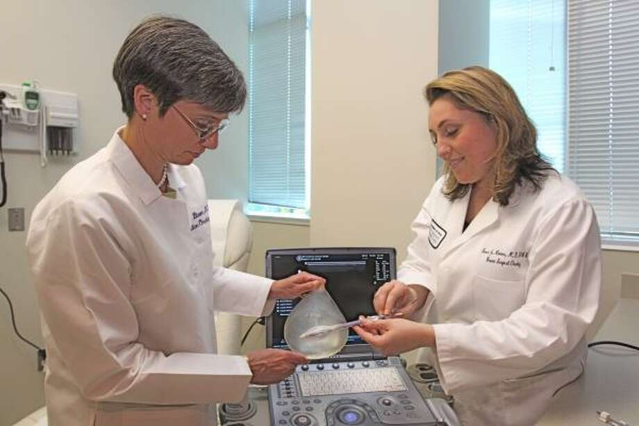 NEW TREATMENT OPTION: Dr. Elizabeth Bloom, left, a board-certified radiation oncologist, and Dr. Susan Hoover, breast surgeon, inserts a catheter into a breast model, demonstrating the new procedure. The ultrasound results are projected on the laptop computer screen. Photo: Suzanne Rehak, For The Chronicle