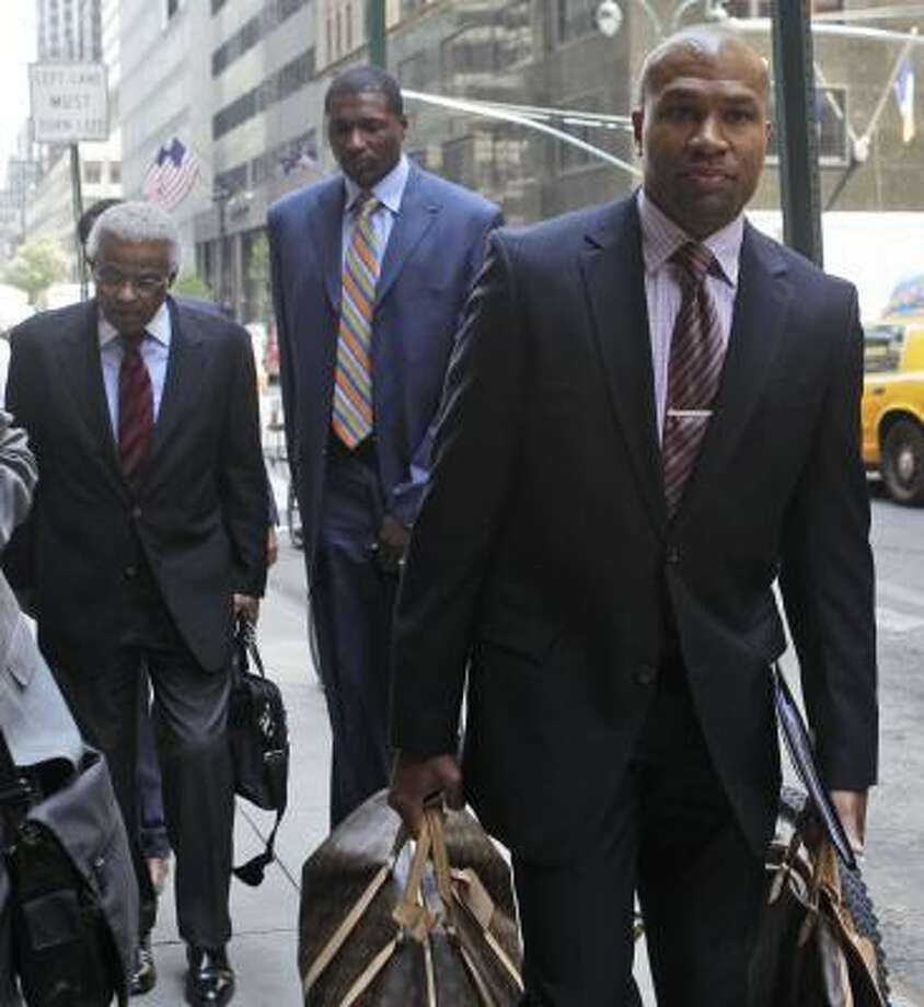 NBA Players Association president Derek Fisher, right, NBA union chief Billy Hunter, left, and Lakers forward Theo Ratliff arrive at a midtown hotel for a meeting with the NBA on Monday in New York. Photo: Mary Altaffer, Associated Press