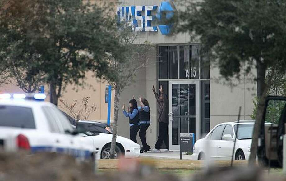 Two hostages and a suspected bank robber leave the Chase bank in Pearland after an hourslong standoff Dec. 31, 2010. Photo: James Nielsen, Chronicle