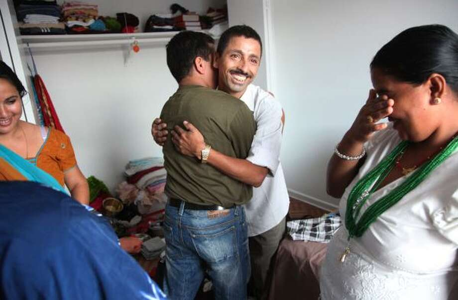 Kushman Dhaurali, center, hugs his brother-in-law Puspa Kheral, who just arrived from Nepal with Kushma's sister, Lachi Kheral, right. The Bhutanese family lived together at a refugee camp in Nepal for nearly 18 years. Photo: Mayra Beltran, Chronicle