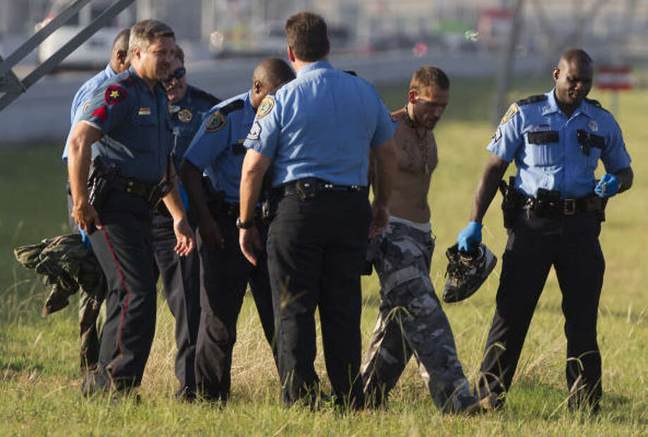Police arrest a man who had climbed to the top of a utility tower just south of Parker Road along the West Hardy Tollway Wednesday, July 20, 2011, in Houston. Photo: Cody Duty, Chronicle