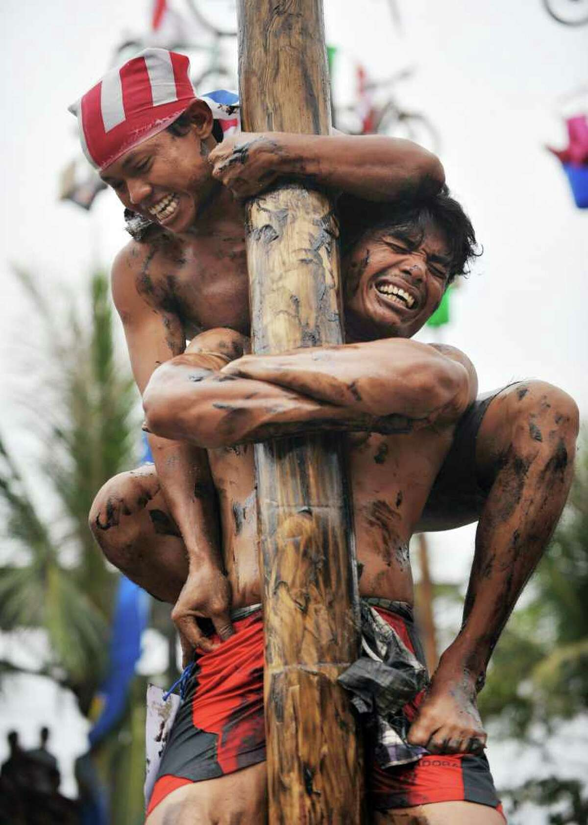 A man holds his friend as they attempt to climb a greased and slippery pole (with prizes attached) to celebrate the Indonesian Independence Day in Jakarta.