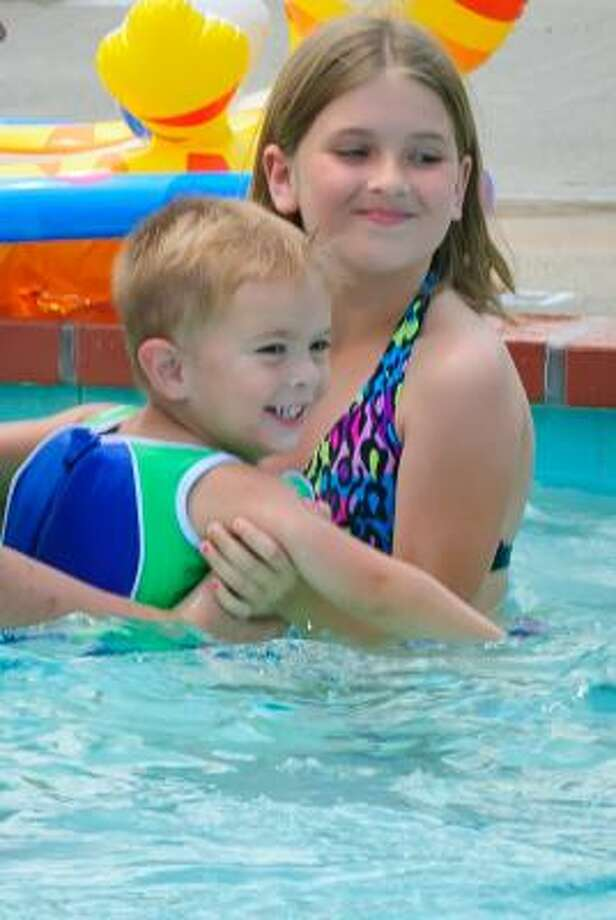 KIM CHRISTENSEN: FOR THE CHRONICLE IN THE POOL: Joshua Dickerson smiles as his sister, Luren, holds onto him at the Seabrook City Pool. Photo: Kim Christensen, For The Chronicle
