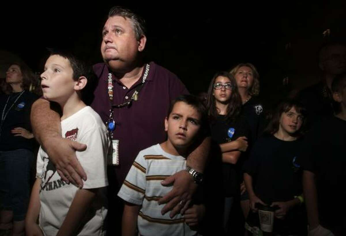 Hundreds watched the landing projected on a large screen at Johnson Space Center. Among them were Steve Cardenas and his sons Spencer, 9, left, and Trever, 7. The Boeing employee called the shuttle