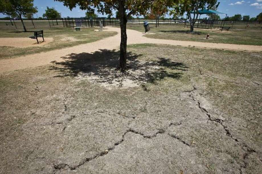 Cracks in the dry ground can be seen at Millie Bush Bark Park on a blistering hot day, Thursday, Aug. 4, 2011, in Houston. Photo: Michael Paulsen, Chronicle