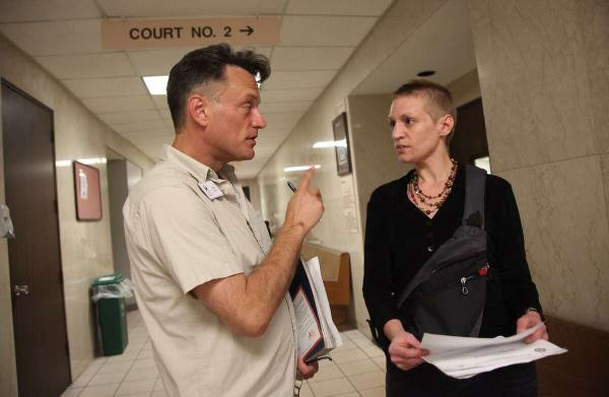 Scot More, community resource manager with Coalition for the Homeless, explains court procedures to Dana Dearman before a Homeless Court session last week. Her tickets for expired inspection and registration stickers were dropped.