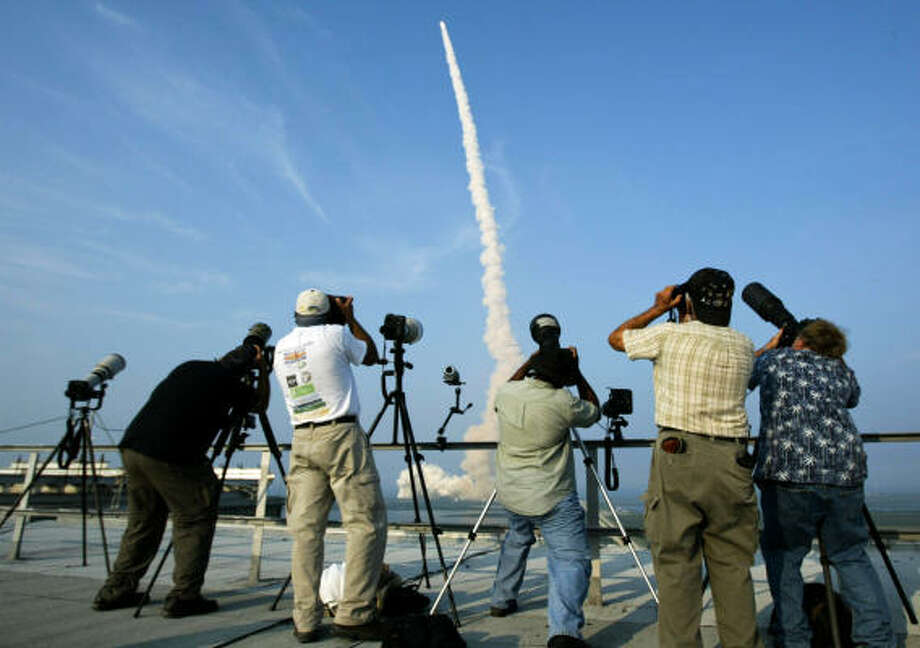 Journalists photograph Endeavour in 2007 as it rockets away from Launch Pad 39A for mission STS-118 to the International Space Station. The photographers took advantage of the view from the roof of NASA's 525-foot-high Vehicle Assembly Building. Photo: James Nielsen, Chronicle