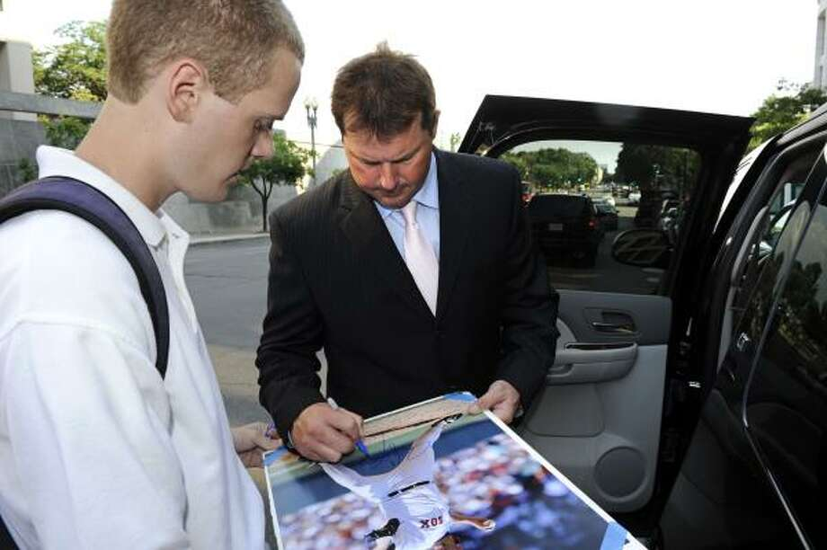Roger Clemens signs a poster from his time with the Red Sox as he leaves court Tuesday. Photo: Cliff Owen, Associated Press