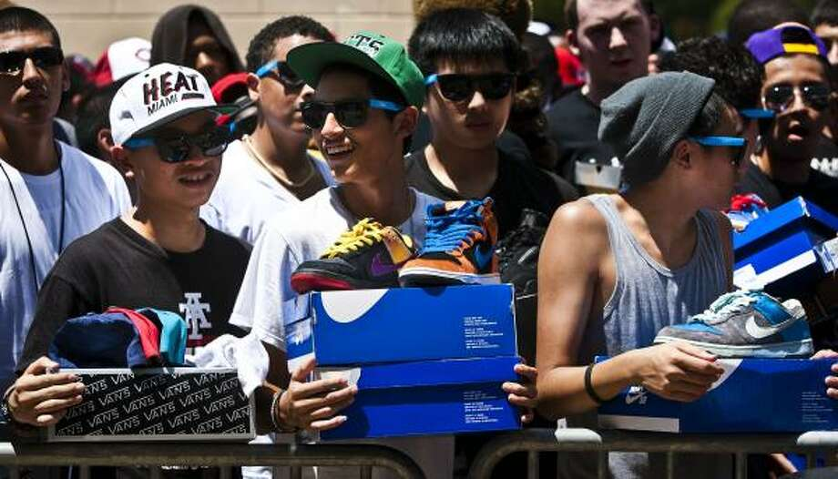 Jimmy Tran, 15, left; Andrew Maldonado, 15; and Derreck Nguyen, 16, wait in line outside with hats and Nike shoes they brought to trade with other collectors and vendors during the H-Town Sneaker Summit at Toyota Center on Sunday. Photo: Patrick T. Fallon, Chronicle