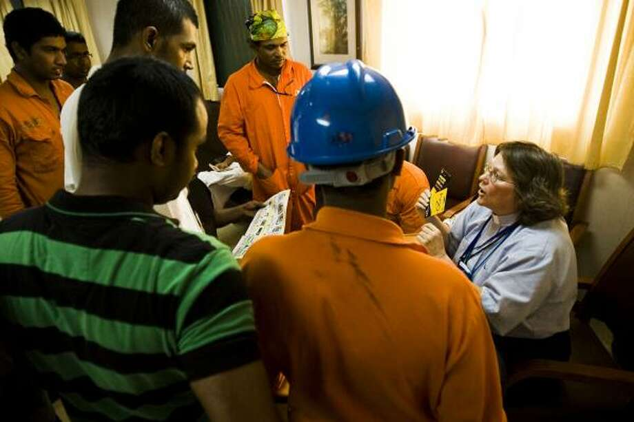 The Rev. Lacy Largent talks to seafarers from India about phone cards and cell-phone SIM cards, which the ministry sells so they can keep in touch with their families. Since 9/11, most sailors are not allowed to leave their ships, and the chaplaincy team must go to them to offer counseling and other services. Photo: PATRICK T. FALLON, CHRONICLE
