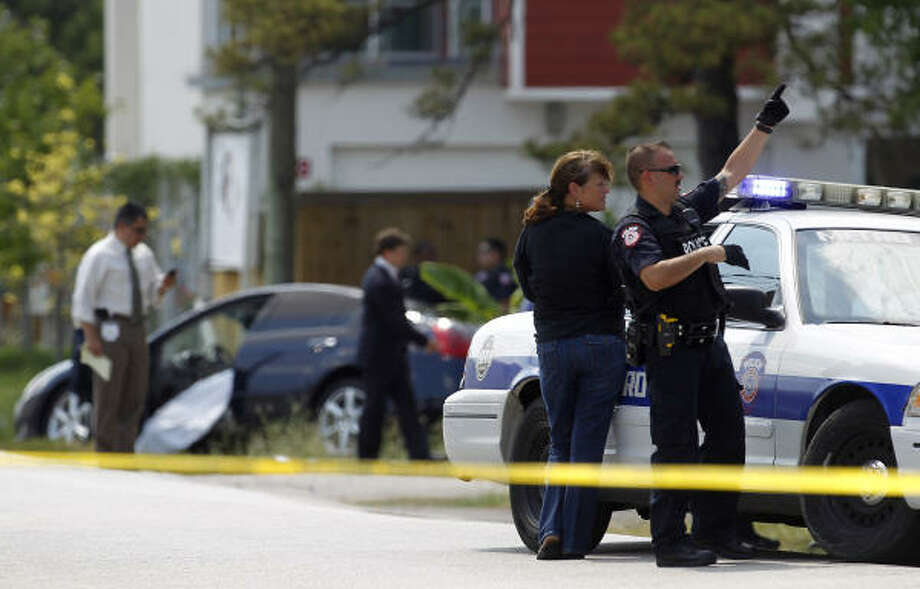 Police talk next to a Metro police car with a suspect in the back seat who was found in an attic after another suspect was shot by an officer Tuesday. Photo: Karen Warren, Houston Chronicle