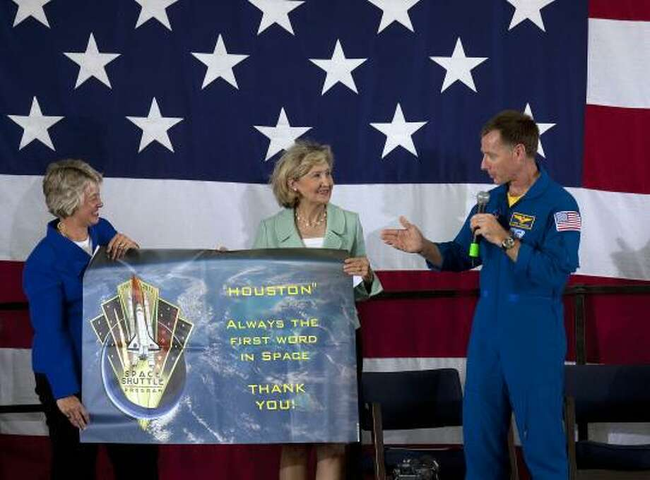 Atlantis shuttle commander Chris Ferguson hands Sen. Kay Bailey Hutchison and Houston Mayor Annise Parker a banner that was flown on space shuttle Atlantis during a homecoming event where hundreds turned out to greet the astronauts at Ellington Field Friday, July 22. Photo: Johnny Hanson, Houston Chronicle