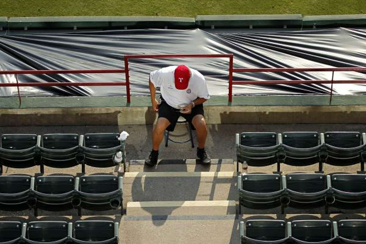 An event staff employee sits in front of the rail where Shannon Stone fell at Rangers Ballpark.