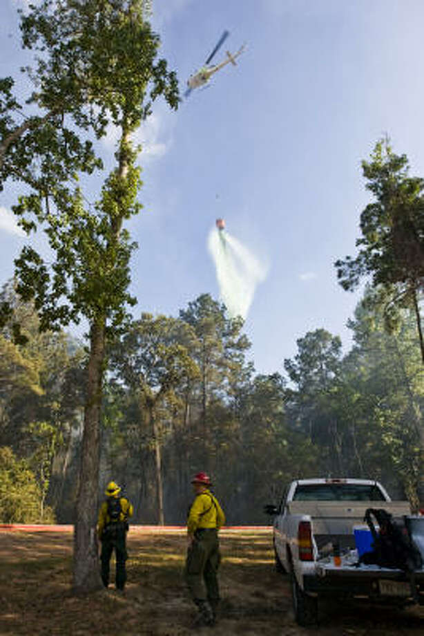 Helicopters douse a wildfire in Spring on Friday. Photo: Patrick T. Fallon, Chronicle