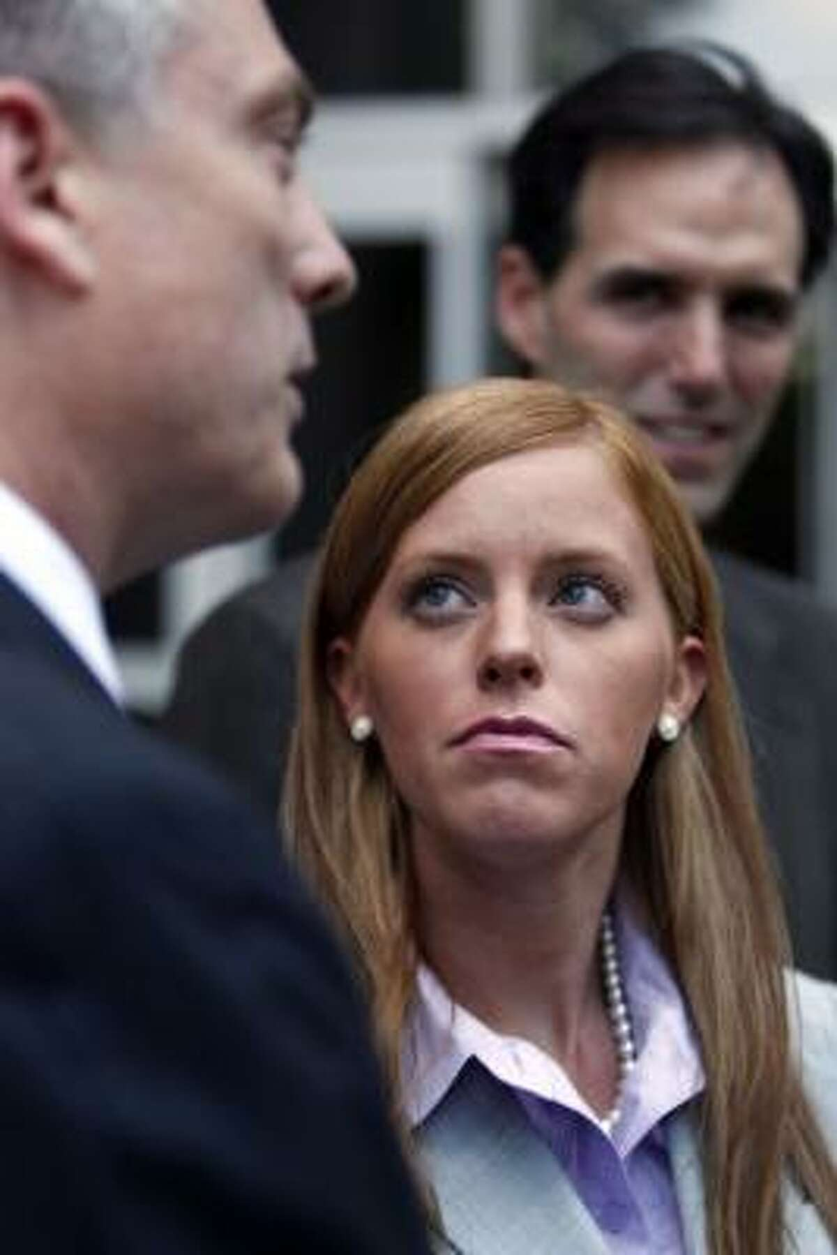 Next to her attorneys Todd Kelly, left, and Ron Estefan, Jamie Leigh Jones,who said she was raped while working for KBR, a Halliburton subsidiary, in Iraq in 2005, watches Kelly speak to the media outside the Bob Casey Federal Courthouse as her civil trial against the company began Tuesday, June 14, 2011, in Houston.